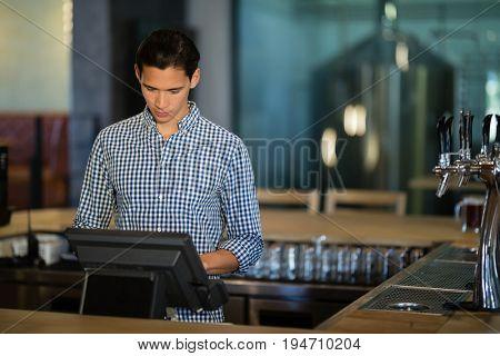 Bar tender operating cash desk at counter in restaurant