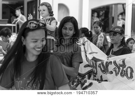BORACAY, WESTERN VISAYAS, PHILIPPINES - JANUARY 11, 2015: Black and white picture of a girl holding Santo Nino statue at Ati-Atihan Festival at White Beach.