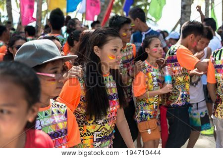 BORACAY, WESTERN VISAYAS, PHILIPPINES - JANUARY 11, 2015: Groups of filipinos with face painted and orange shirts during Ati-Atihan Festival at White Beach.