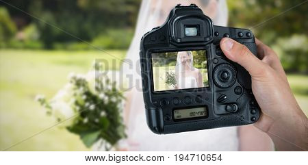 Cropped hand of photographer holding camera  against bride looking away through veil
