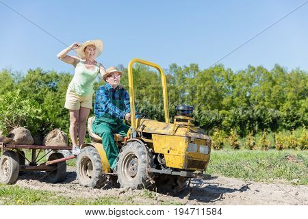 Grandfather taking grandmother for ride on tractor trailer across countryside field in summer. Family time, hapiness and joy. Active retirement