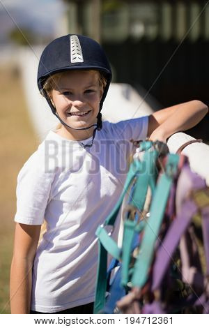 Portrait of smiling girl leaning on the fence next to horse reins and muzzle