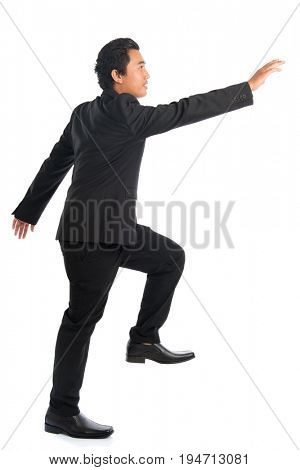 Full body side view of attractive young Southeast Asian businessman stepping up stair case and hand grabbing something, isolated on white background.