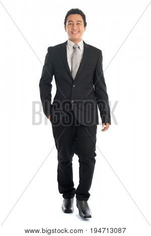 Full length front view portrait of attractive young Southeast Asian businessman walking, isolated on white background.