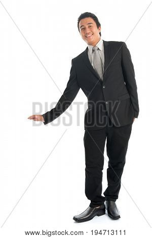Full body portrait of young Southeast Asian businessman hand leaning on invisible object, standing isolated on white background.