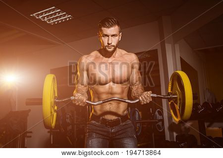 man in gym. Muscular bodybuilder guy doing exercises with barbell. Strong person. Sports background. Young athlete ready for weight lifting training. Flare for text and design