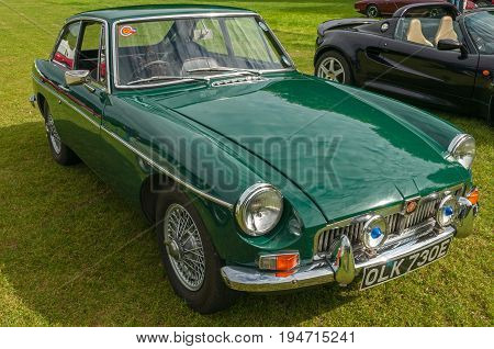 Green MBG GT, Hull, East Yorkshire, England, 11th June 2017, Classic British MG Sports Car, side  and front view of  green MGB GT sports car, at East Park Classic Car Run.