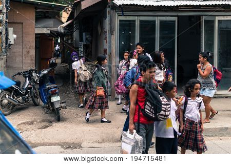 BORACAY, WESTERN VISAYAS, PHILIPPINES - JANUARY 12, 2015: Filipino children coming back from school dressed with skirts in Boracay Philippines.