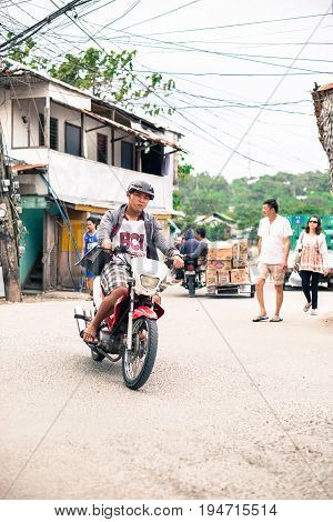 BORACAY, WESTERN VISAYAS, PHILIPPINES - JANUARY 12, 2015: Man riding a motorcycle with people walking in the streets of Boracay.