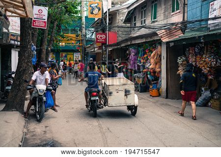 BORACAY, WESTERN VISAYAS, PHILIPPINES - JANUARY 12, 2015: People walking and riding motorcycle in a street with many small stores in Boracay.