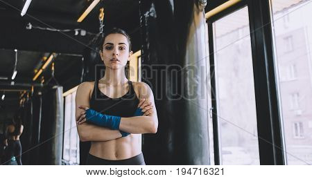 Serious smiling woman standing with crossed arms in the gym near the window, Sporty girl has wrapped her fists with blue cloth. Close up