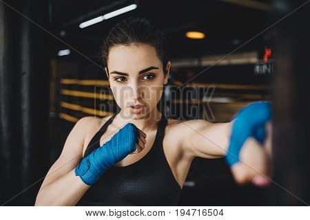 Pretty girl training with punching bag in the gym. Hardworking woman effectively working on her punches with some aggression. Close up