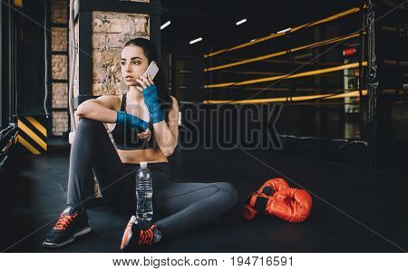 Worn out and serious cute woman with wrapped fists for fighting resting on the floor in gym after effective training and calling her friends on mobile