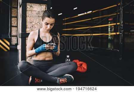 Attractive woman in sportswear sitting near the boxing ring and having some rest. She is scrolling in her mobile phone or chatting with friends