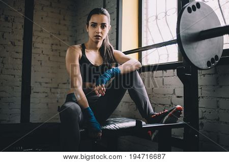 Confident and concentrated young female looking at the camera and resting on the powerlifting machine with placed leg on the top