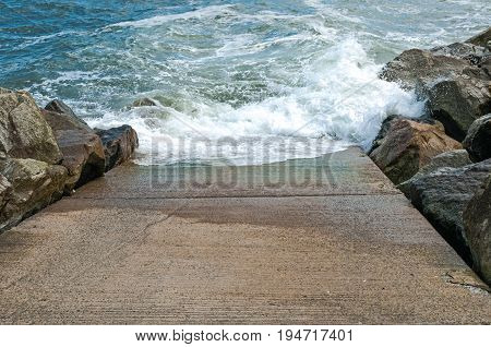 Stone slipway with blue ocean sea breaking waves and rocks