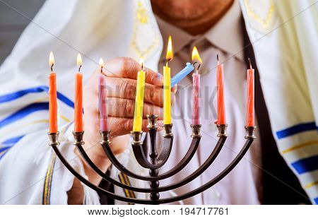 man hand lighting candles in menorah on table served for Hanukkah
