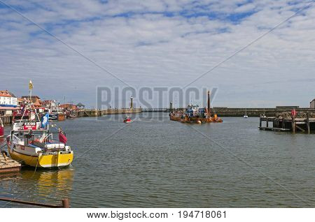 Whitby, United Kingdom - July 13, 2016: Whitby Harbour,Charter fishing boat tied up at dock, River Esk, Whitby North Yorkshire. Dredger in mid river with the harbour piers in distance.