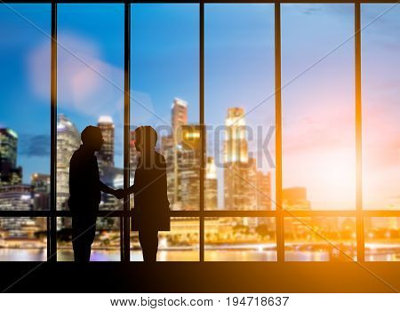 Success of the joint venture business growth progress and potential concepts.Silhouette businessmen shake hands finishing a deal between businesses over blurred employees the city night.flare light