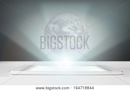 Working a hologram of the earth on the tablet. omnichannel icon flow.Elements of this image are furnished by NASA
