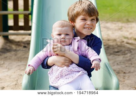 Cute little kid boy with newborn baby girl, cute sister. Siblings on playground in summer or spring on mother's day. Brother holding baby girl on arm. Kids bonding.