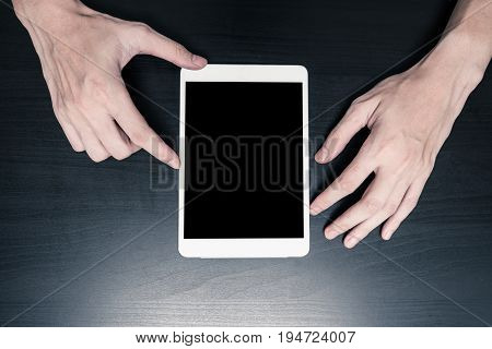 Close up of Male hands using tablet on the table.