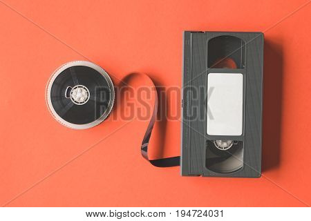 Video cassette tape and reel on orange background.