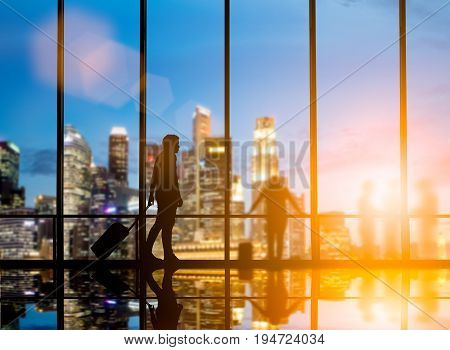 Young travelers dragging suitcases walked to travel abroad in the bus terminal would leave the country over blurred other travelers waiting plane and city at night interior with large windows.