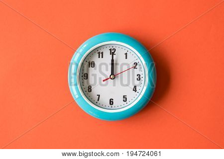 Blue wall clock on orange background twelve o'clock