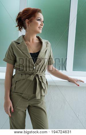 Beautiful brown haired woman in nice khaki jacket and pants posing near the window studio portrait