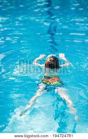 Happy little preschool kid boy making swimming competition. Child having fun in an swimming pool. Active happy child winning. sports, active leisure for children