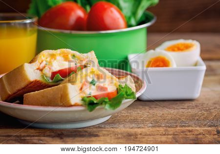 Pocket sandwich for breakfast or lunch. Homemade sandwich with hard boiled eggs and mayonnaise decorated by lettuce and tomato. Baked sandwich on lovely plate serve with orange juice on rustic wood table. Delicious homemade sandwich.