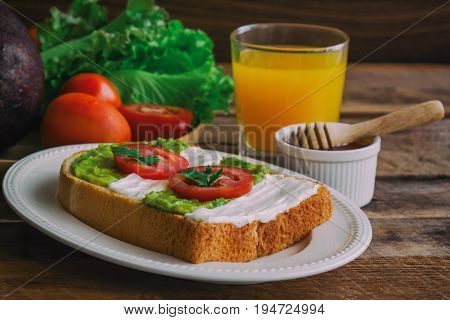 Open sandwich for breakfast or lunch. Healthy sandwich spread with cream cheese avocado and tomato. Avocado and cream cheese open sandwich style serve with orange juice on rustic wood table. Delicious homemade sandwich ready to served.