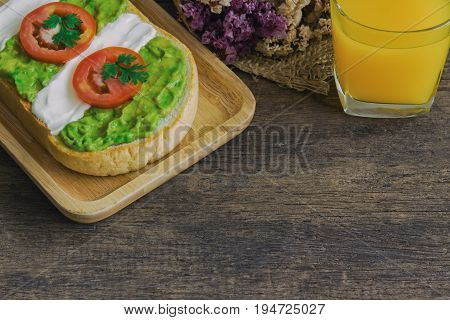 Open sandwich for breakfast or lunch. Healthy sandwich spread with cream cheese avocado and tomato. Avocado and cream cheese open sandwich style serve with orange juice on wood table with copy space. Delicious sandwich ready to served.