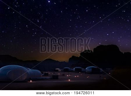 Milky Way and a lot of stars over the mountain at Wadi Rum desert. Sky at night and silhouette of mountain with wonderful landscape in summer concept for space background and traveling.
