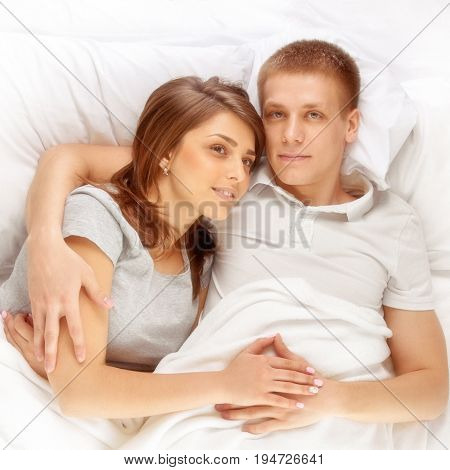 Young happy loving couple lying in bed together. image with toning
