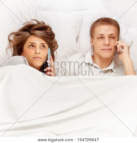 Concentrated young man and woman lying in bed and talking on phones. image with toning