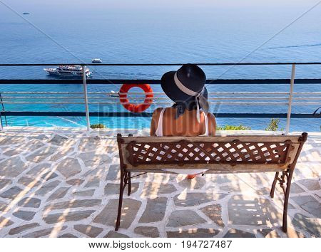 A woman is resting on a bench with a view of the Ionian Sea and ships with tourists. Zakynthos.