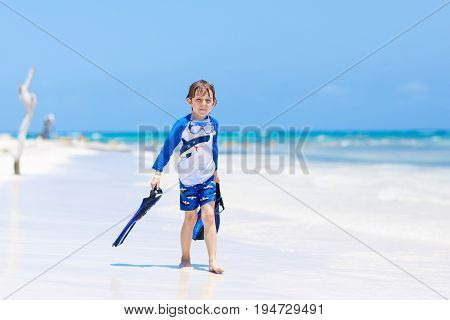 Adorable little blond kid boy having fun on tropical beach of Jamaica. Excited child playing and surfing in sun protected swimsuit in ocean on vacations. White sand, Kid holding flippers for swimming