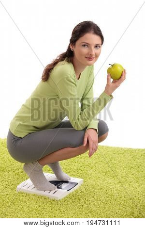 Healthy teenage girl crouching on bathroom scale, holding apple, looking at camera, smiling.