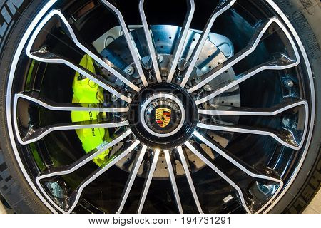 STUTTGART GERMANY - MARCH 17 2016: Wheel and brake system of a mid-engined plug-in hybrid sports car Porsche 918 Spyder 2015. Close-up. Europe's greatest classic car exhibition