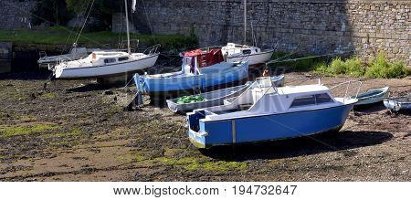 Blue and White Fishing boats moored at low tide in the Cornish harbour England UK