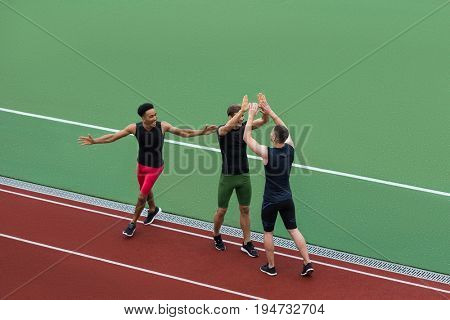 Image of smiling multiethnic athlete team standing on running track outdoors make winner gesture and gives a high-five to each other. Looking aside.