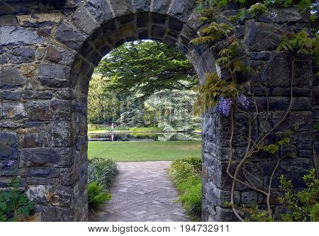 A hidden stone arched gate is opening up to a beautiful English style garden and pond