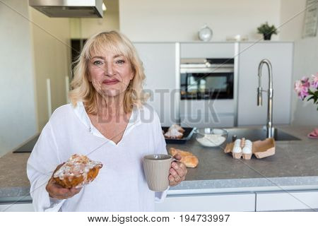 Smiling mature lady holding cup of coffee and freshly baked muffin while standing on a kitchen