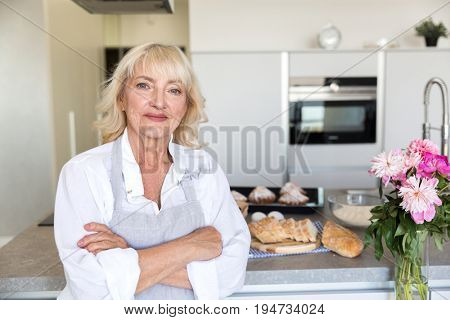 Smiling mature woman in apron standing with arms folded and looking at camera at her kitchen