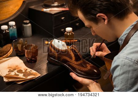 Picture of young concentrated shoemaker in workshop making shoes. Looking aside.
