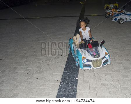 Happy laughing girl driving a toy car at night. Energy, joy, playfulness, determination in the look of the little mixed ethnicity girl with curly hair