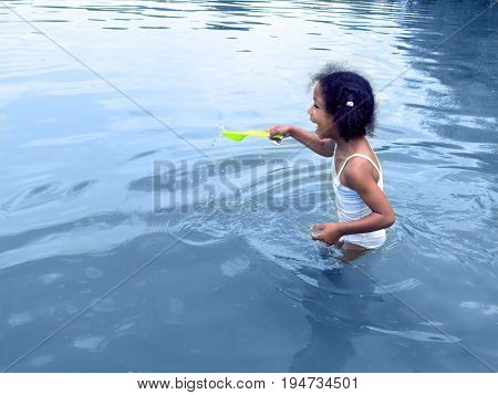 Little girl playing with toy shovel in lake water. Happy laughing little mixed ethnicity  girl with curly hair