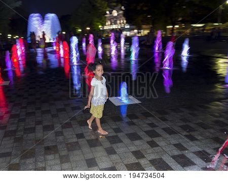 Waggish little girl barefoot at the night on a fountain with a color effect. Emphatic look of the bright child that enjoy getting wet with the jet of water  during the summer vacation, motion blur
